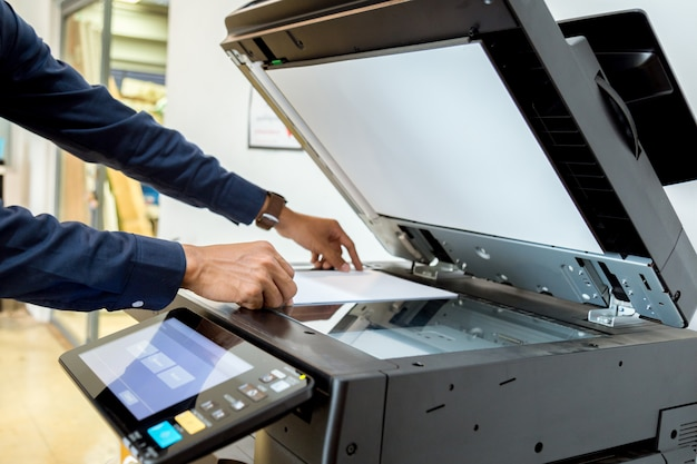 Geschäftsmann handpresseknopf auf platte des druckers, druckerscannerlaser-bürokopiermaschinenversorgungen beginnen konzept. Premium Fotos