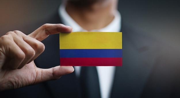 Geschäftsmann holding card von kolumbien flagge Premium Fotos