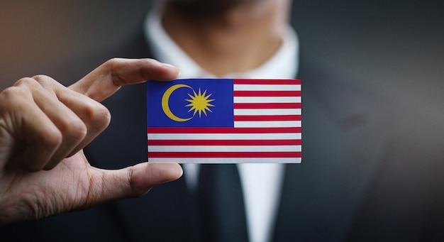 Geschäftsmann holding card von malaysia flagge Premium Fotos