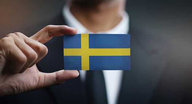Geschäftsmann holding card von schweden flagge Premium Fotos
