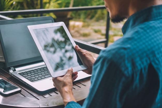 Geschäftsmann holding tablet mit einem mobile und einem laptop auf dem tisch Premium Fotos