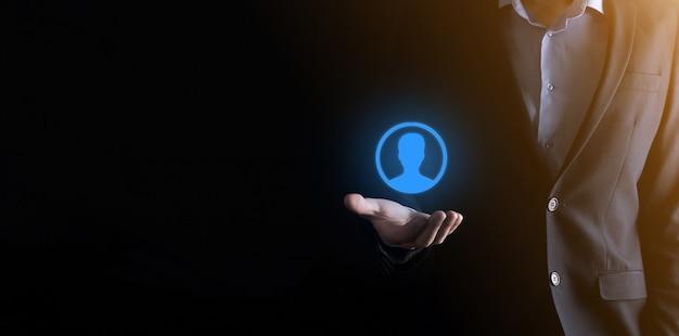 Geschäftsmann im anzug, der handsymbol des benutzers heraushält. vordergrund der internet-symbole Premium Fotos