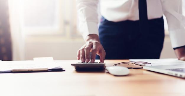Geschäftsmann im büro und im gebrauch computer und taschenrechner, zum von finanzbuchhaltung durchzuführen Premium Fotos