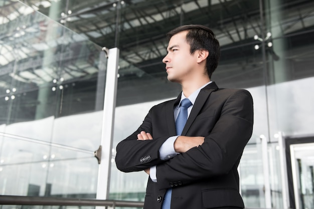 Geschäftsmann im dunkelgrauen anzug, der seine arme kreuzt Premium Fotos