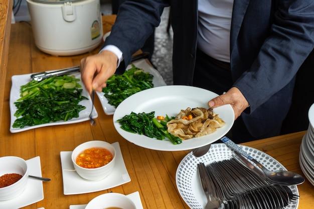 Geschäftsmann im geschäftsanzug, der die gebratene nudel mit schweinefleisch und brokkoli zum mittagessen vorbereitet. Premium Fotos