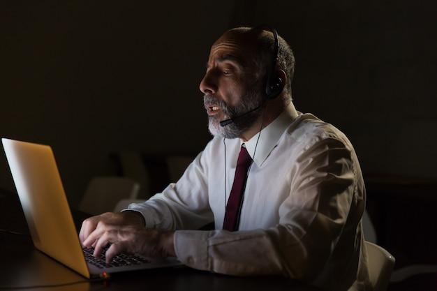Geschäftsmann im kopfhörer sprechend und laptop verwendend Kostenlose Fotos
