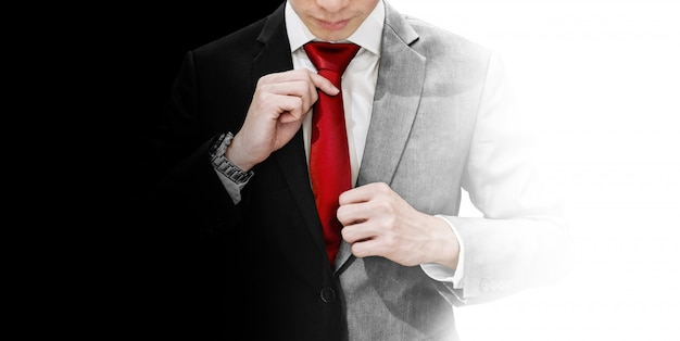 Geschäftsmann im leeren und weißen anzug, der rote krawatte bindet Premium Fotos