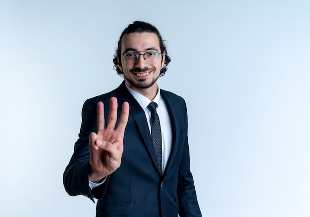 Geschäftsmann im schwarzen anzug und in den gläsern, die mit den fingern nummer drei lächelnd zeigen und über der weißen wand stehend zeigen Kostenlose Fotos