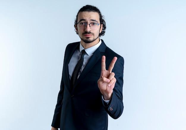 Geschäftsmann im schwarzen anzug und in der brille, die mit den fingern nummer zwei zeigt und zeigt, die mit ernstem gesicht über weißer wand stehen Kostenlose Fotos