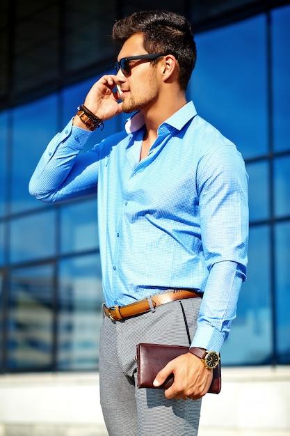 Geschäftsmann in der formalen kleidung und in der sonnenbrille unter verwendung seines telefons Kostenlose Fotos