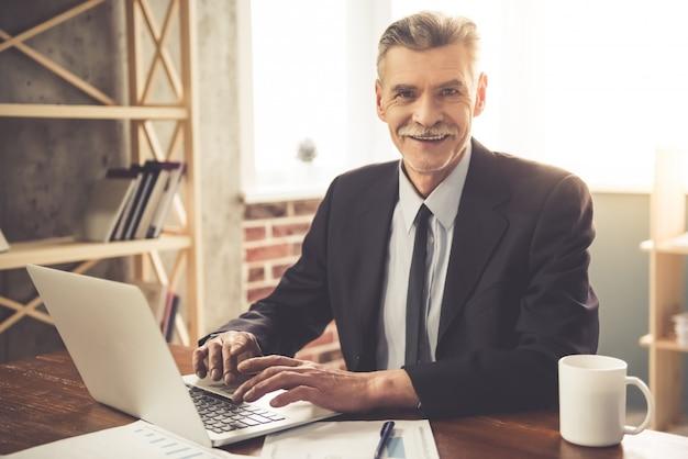 Geschäftsmann in der klassischen kleidung betrachtet kamera. Premium Fotos
