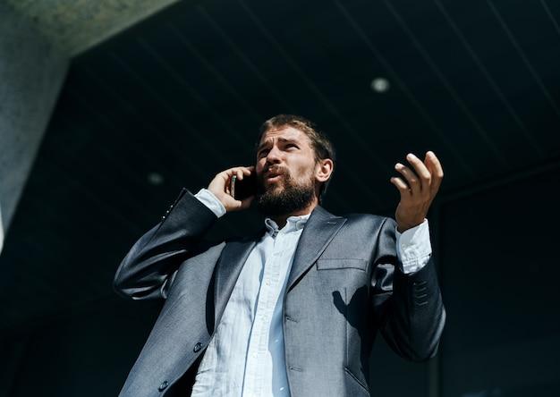 Geschäftsmann in einem anzug, der am telefon im freien business manager executive spricht Premium Fotos