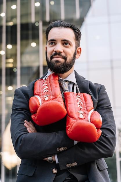 Geschäftsmann in einem anzug, in einer uhr und in boxhandschuhen, die von seinem hals mit seinen händen hängen, kreuzte vor einigen gebäuden Kostenlose Fotos