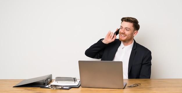 Geschäftsmann in einem büro, das ein gespräch mit dem handy hält Premium Fotos