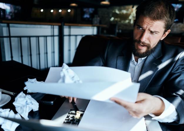 Geschäftsmann in einem café, das am tisch sitzt, dokumentiert laptop zerknitterte papier executive lifestyle emotionen Premium Fotos
