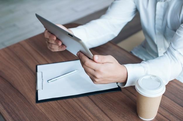 Geschäftsmann in einem weißen hemd mit einem digitalen tablett in seinen händen unterschreibt einen vertrag im büro Premium Fotos