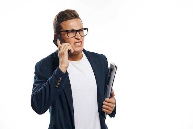 Geschäftsmann in einer jacke mit brille, die am telefon spricht Premium Fotos