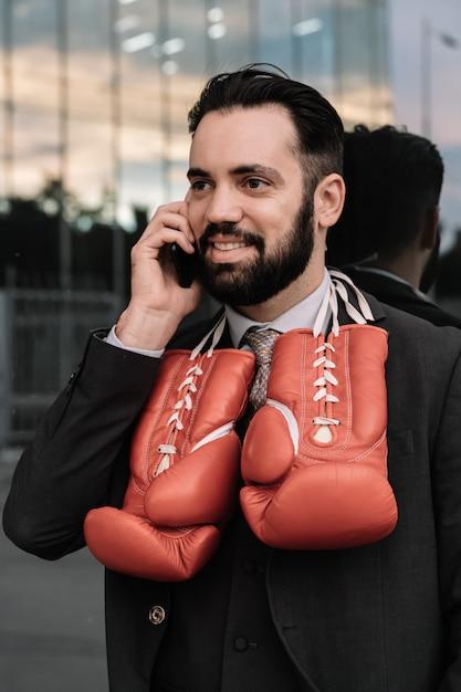 Geschäftsmann in einer klage sprechend an seinem handy mit den roten boxhandschuhen, die von seinem halslehnen hängen Kostenlose Fotos