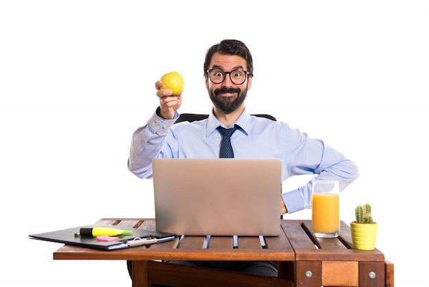 Geschäftsmann in seinem büro mit einem apfel Kostenlose Fotos
