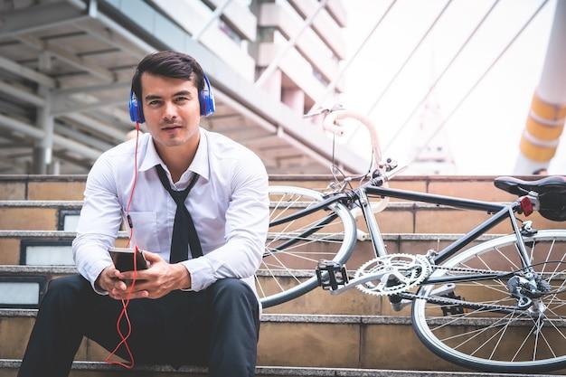 Geschäftsmann ist entspannend musik mit seinem fahrrad auf der seite hören Premium Fotos