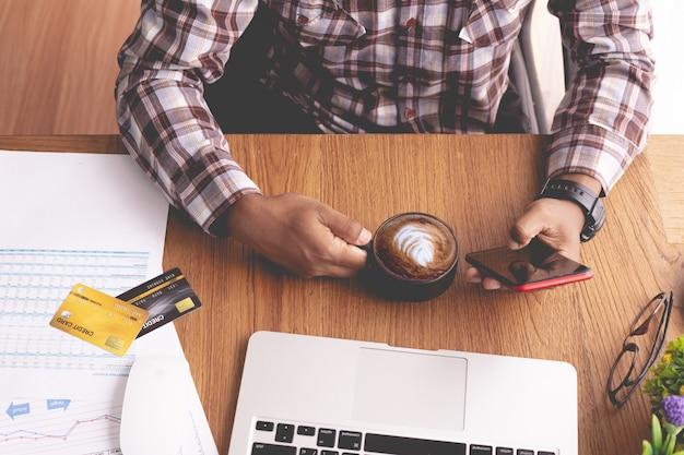 Geschäftsmann kaffee trinken und mit telefon am schreibtisch Premium Fotos
