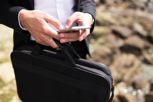 Geschäftsmann mit aktenkoffer sms nachricht im freien Kostenlose Fotos