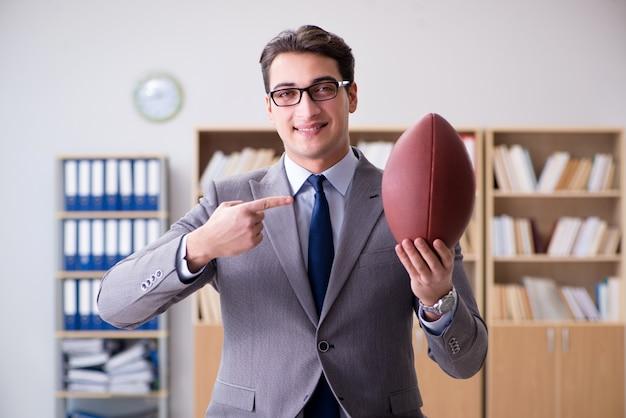Geschäftsmann mit amerikanischem fußball im büro Premium Fotos