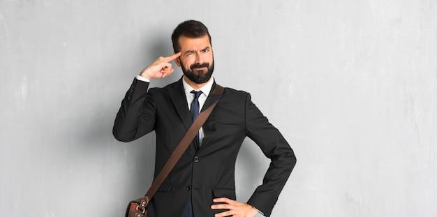Geschäftsmann mit dem bart, der die geste des wahnsinns finger auf den kopf setzt Premium Fotos