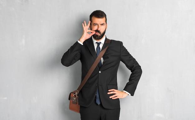 Geschäftsmann mit dem bart, der ein zeichen des schließens der mund- und ruhegeste zeigt Premium Fotos