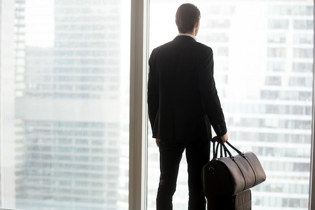 Geschäftsmann mit dem gepäck, das vor großem fenster steht. Kostenlose Fotos