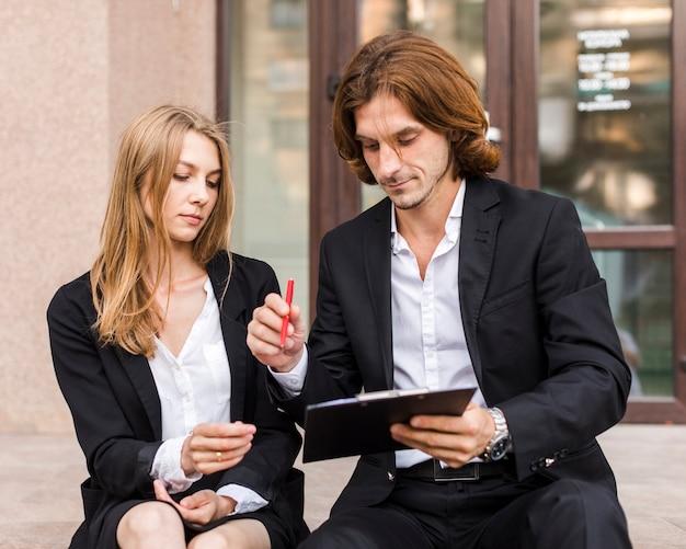 Geschäftsmann mit dem sekretär, der auf einem klemmbrett unterzeichnet Kostenlose Fotos