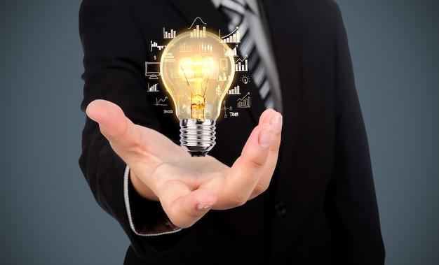 Geschäftsmann mit einer glühbirne in der hand Kostenlose Fotos