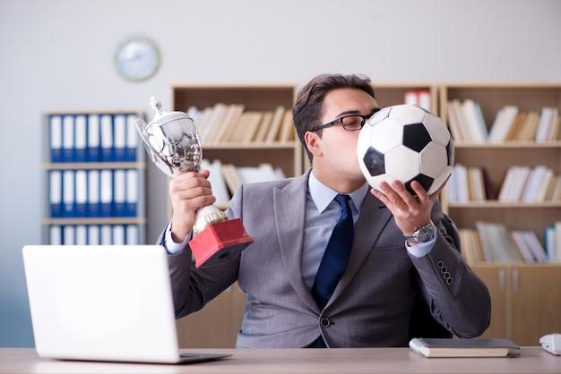 Geschäftsmann mit fußball im büro Premium Fotos