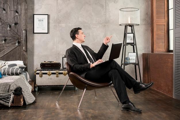 Geschäftsmann mit laptop weg zeigend und erwägen Kostenlose Fotos