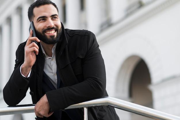 Geschäftsmann mit niedrigem winkel, der über telefon spricht Kostenlose Fotos