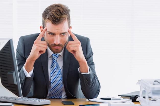 Geschäftsmann mit schweren kopfschmerzen am schreibtisch Premium Fotos