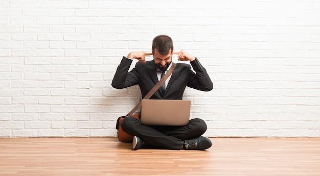 Geschäftsmann mit seinem laptop, der auf dem boden sitzt, der beide ohren mit den händen bedeckt Premium Fotos
