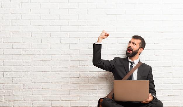 Geschäftsmann mit seinem laptop, der auf dem boden sitzt, einen sieg in der siegerposition feiernd Premium Fotos