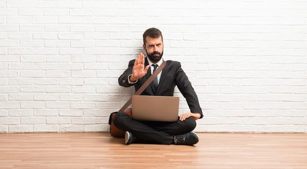 Geschäftsmann mit seinem laptop, der auf dem boden sitzt, machend die stoppgeste, die eine situation ablehnt, die falsch denkt Premium Fotos