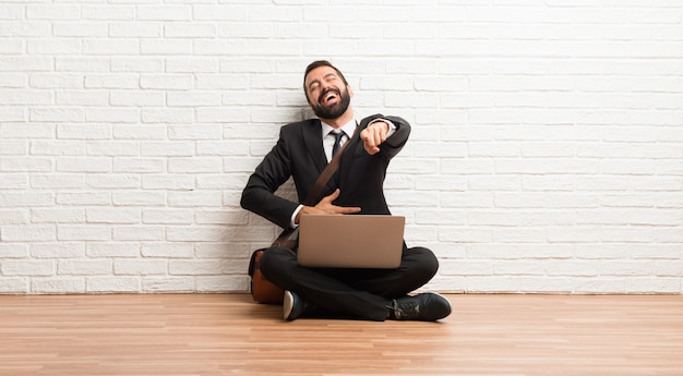 Geschäftsmann mit seinem laptop, der auf dem boden sitzt mit finger auf jemand zeigend und viel lacht Premium Fotos
