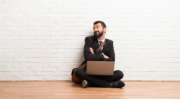 Geschäftsmann mit seinem laptop, der auf dem boden sitzt und zweifel machen lässt, gestikulieren beim anheben der schultern Premium Fotos