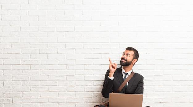 Geschäftsmann mit seinem laptop, der auf dem fußboden sitzt, eine großartige idee zeigend und oben schauend Premium Fotos