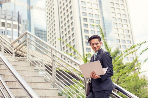 Geschäftsmann mit seinem laptop, der die treppe in einer hauptverkehrszeit hinaufgeht, um zu arbeiten Premium Fotos