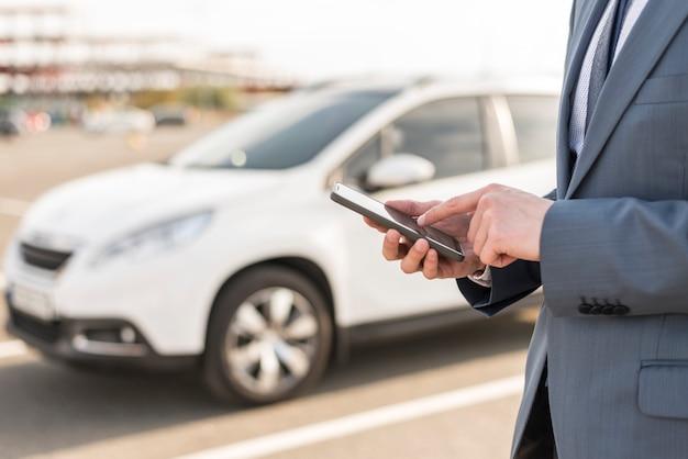 Geschäftsmann mit smartphone vor dem auto Kostenlose Fotos