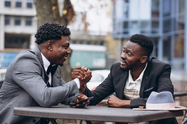Geschäftsmann mit zwei afrikanern, der außerhalb des cafés sitzt Kostenlose Fotos