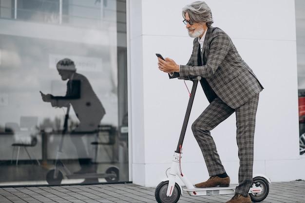 Geschäftsmann mittleren alters, der roller in einem noblen anzug reitet Kostenlose Fotos