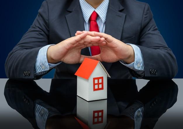 Geschäftsmann oder immobilienmakler und halten eines musterhauses Premium Fotos