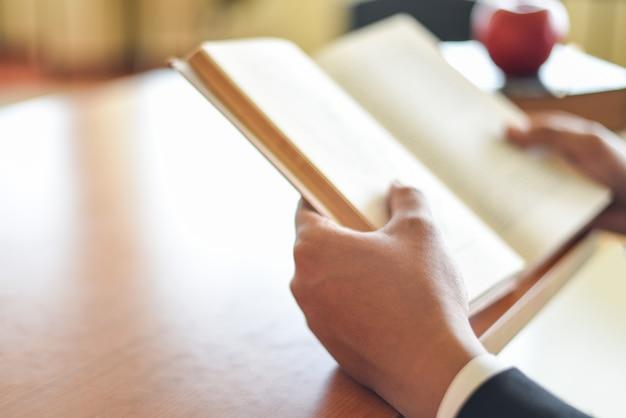Geschäftsmann oder student, der ein buch zur hand hält - geschäftsbildungsstudienkonzeptmann, der buch auf dem tisch liest Premium Fotos