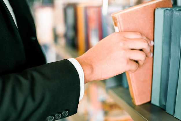 Geschäftsmann oder student, der ein buch zur hand hält oder ein buch auf bücherregal im hintergrund der bücherregale der bibliothek auswählt - business education study concept Premium Fotos
