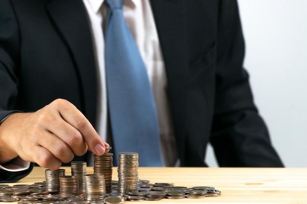 Geschäftsmann steckte münzenstapelgeld Premium Fotos